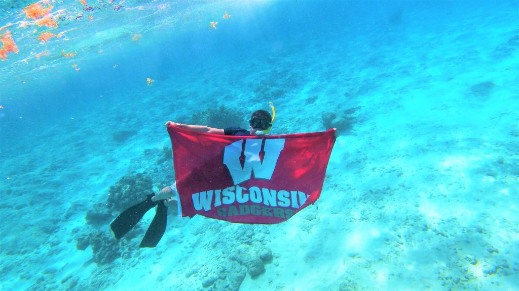 Luis Abreu-Socorro holding UW Madison Badgers flag underwater while at Turks and Caicos study abroad program